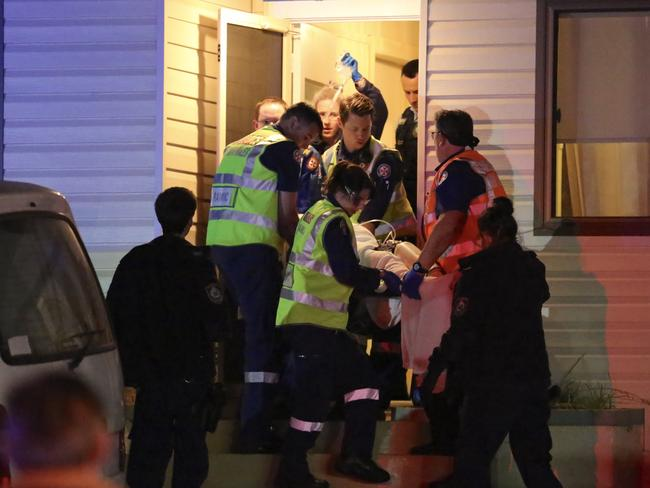 Emergency crews remove the burns victim from the scene. Picture: Steve Tyson