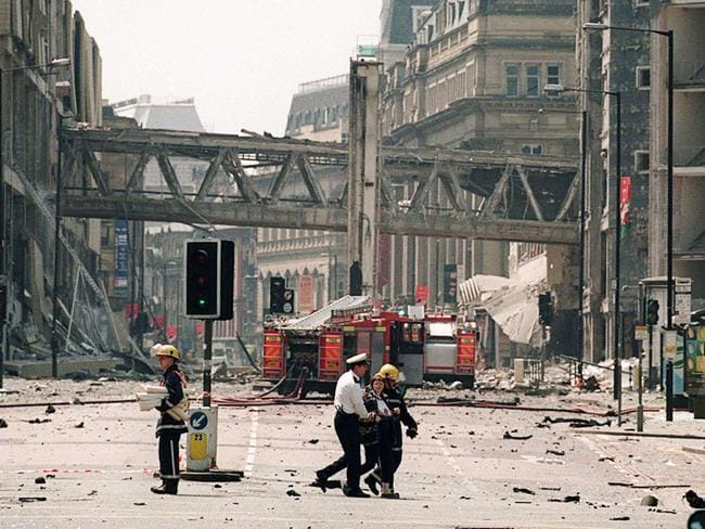 Emergency workers guide an injured person across a deserted rubble strewn street in central Manchester, 1996. Picture: AP/Howard Barlow