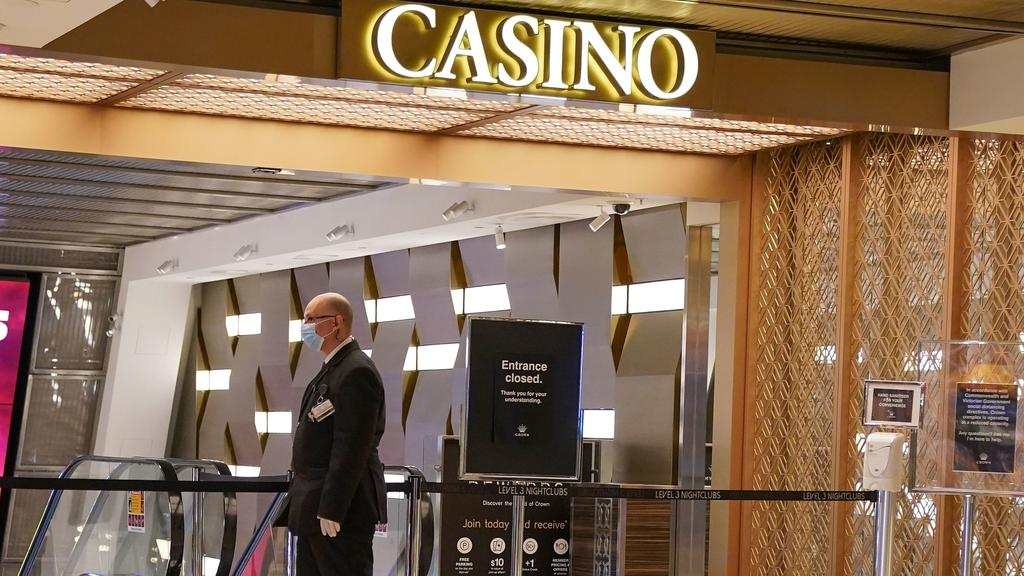 A security guard patrols a closed entrance outside Crown Casino today. Picture: AAP Image/Scott Barbour