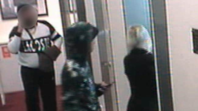 The man in white barged his way into a room with the young woman and man in green (pictured) moments after this footage of him following them was recorded.