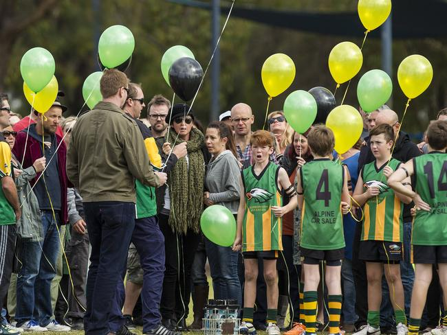 Parents of Mo, Evie and Otis Maslin, Anthony Maslin (in red jacket and hat) and Rin Norris (scarf, black hat) are comforted by friends and supporters as they release balloons after Mo's club's junior football match. Picture: Will Russell