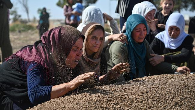 People mourn in front of the grave of a Kurdish civilian who was killed in a mortar attack in Suruc near northern Syria border. Picture: AFP