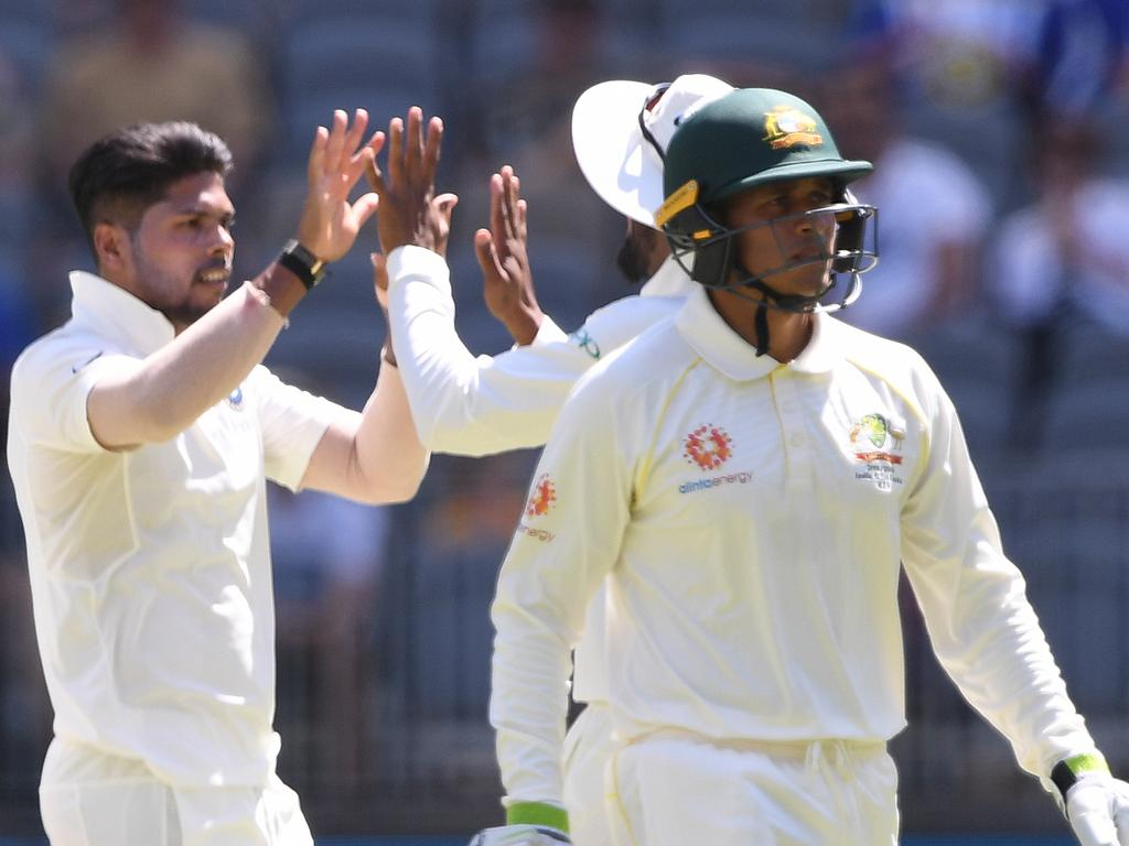 Australian batsman Usman Khawaja departs for 5 runs after being dismissed by Indian bowler Umesh Yadav (left) on day one of the second Test match between Australia and India at Perth Stadium in Perth, Friday, December, 14 2018.  (AAP Image/Dave Hunt) NO ARCHIVING, EDITORIAL USE ONLY, IMAGES TO BE USED FOR NEWS REPORTING PURPOSES ONLY, NO COMMERCIAL USE WHATSOEVER, NO USE IN BOOKS WITHOUT PRIOR WRITTEN CONSENT FROM AAP