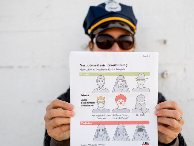 This illustration photo shows a model holding up an information pamphlet about new Austrian restrictions banning the wearing of burqas and other items covering the face in public places. Picture: AFP.