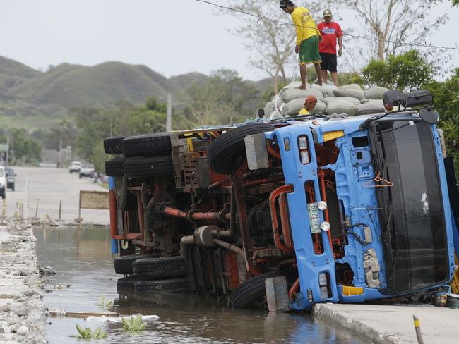 Workers transfer sacks of grains from a toppled truck that fell into an area where the road was being repaired following floodwaters in northeastern Philippines on Sunday. Picture: AP Photo/Aaron Favila