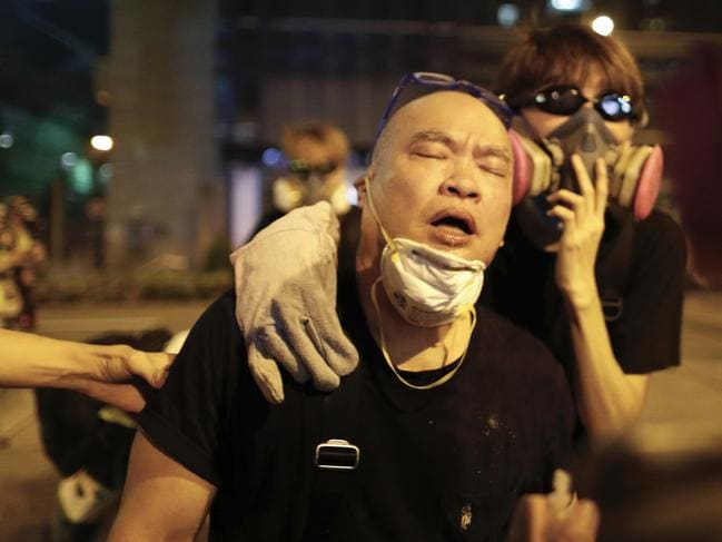 A protester is overcome by tear gas near the Shum Shui Po police station in Hong Kong on Wednesday. Picture: AP
