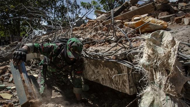 An Indonesian soldier looking for victims at a collapsed house in Lombok Island. Picture: Ulet Ifansasti/Getty Images