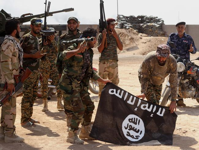 Terror group grows ... Iraqi security forces hold a flag of the Islamic State group they captured during an operation outside Amirli, north of Baghdad, Iraq. Picture: AP