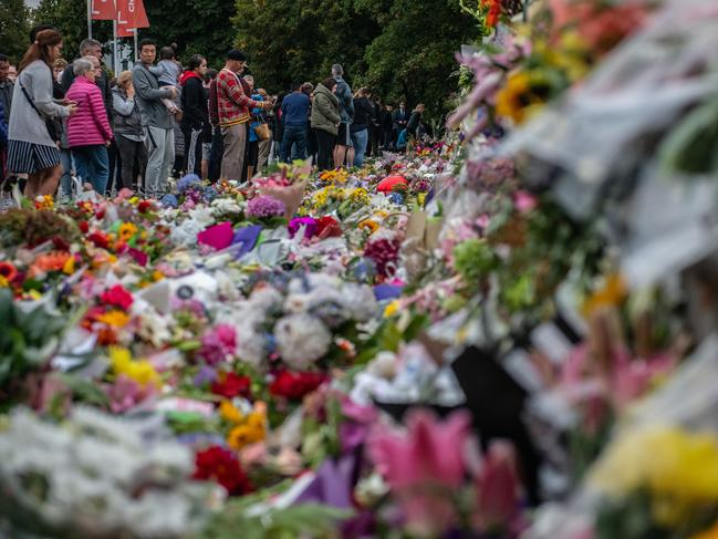 People pause next to flowers and tributes for the victims of the massacre. Picture: Getty