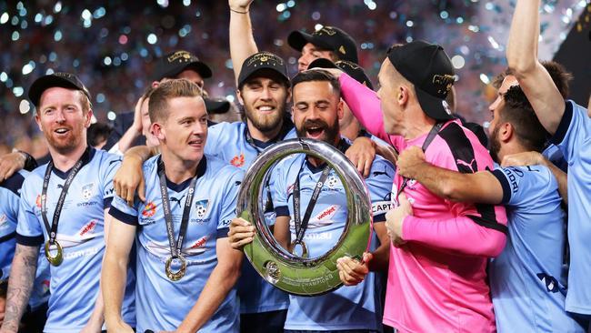 Alex Brosque captain of Sydney FC holds aloft the A-League trophy.