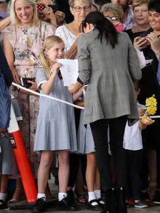 An adoring fan hands Meghan a poster.