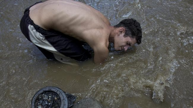 David Garcia keeps his head just barely above water as he scrapes the bottom of the polluted Guaire River in search of gold and anything of value to sell in Caracas to put food on the table. Picture: AP/Ariana Cubillos