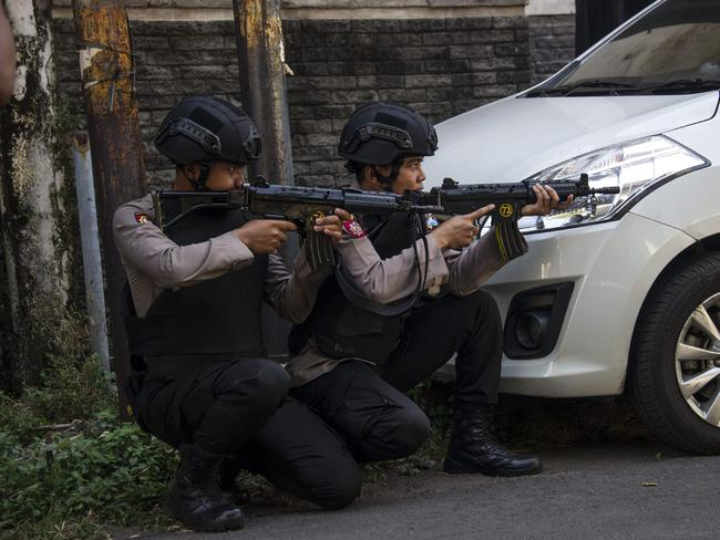 Mobile brigade police take position as they patrol outside the Surabaya police headquarters following a suicide attack in Surabaya. Picture: AFP