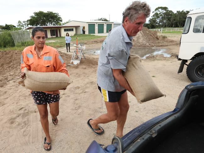 Bowen locals, including Rena Singh and Jim Gaffney, fill sand bags on Sunday. Picture: Lyndon Mechielsen