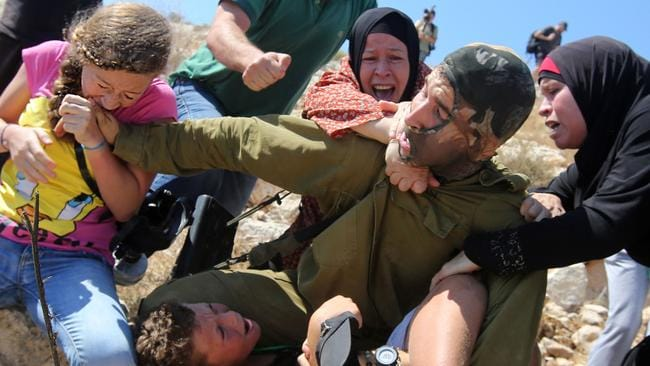This photo shows Palestinian Ahed Tamimi (L) fighting with other members of her family to free her brother (bottom) held by an Israeli soldier (C) during clashes with Israeli security forces