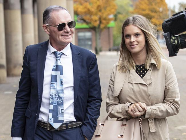 Former soccer player Paul Gascoigne leaves court, accompanied by unidentified woman, after giving evidence. (Danny Lawson/PA via AP)