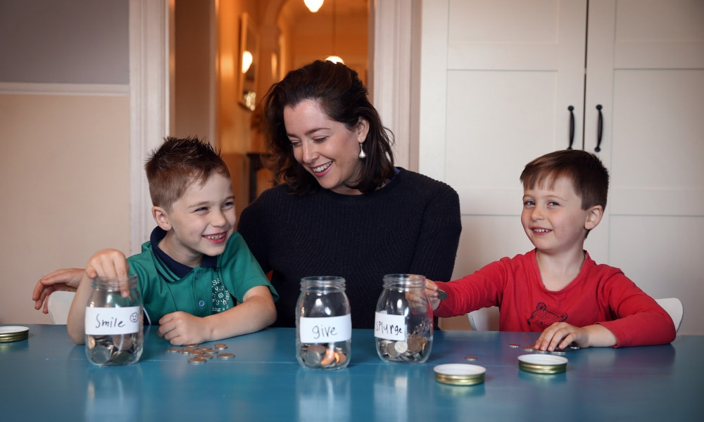 "SUNDAY TELEGRAPH - 21/9/18 Georgie Gonczi with kids Monty (7 yrs in green) and Louis (4yrs in red) pictured with their ""Barefoot Investor"" jars. Pic, Sam Ruttyn"
