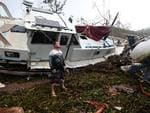 Bradley Mitchell inspects the damage to his uncle's boat after it smashed against the bank at Shute Harbour, Airlie Beach, Wednesday, March 29, 2017. Picture: AAP Image/Dan Peled