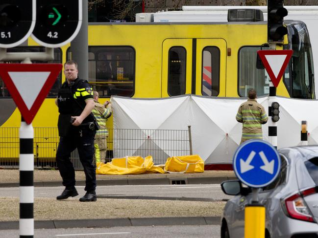Rescue workers install a screen on the spot where a body was covered with a white blanket following a shooting in Utrecht, Netherlands on Monday. Picture: AP Photo/Peter Dejong