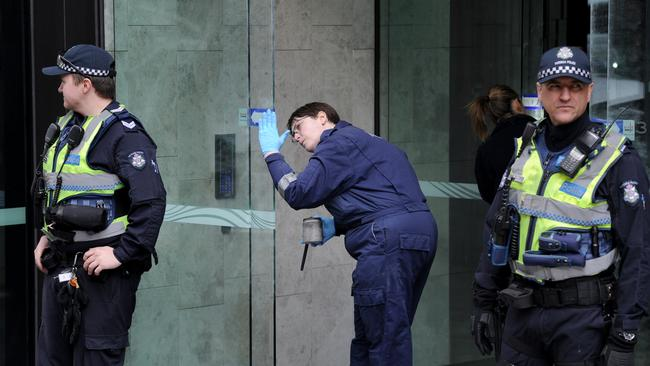 Forensic police examine the entrance to EQ Tower. Picture: Andrew Henshaw