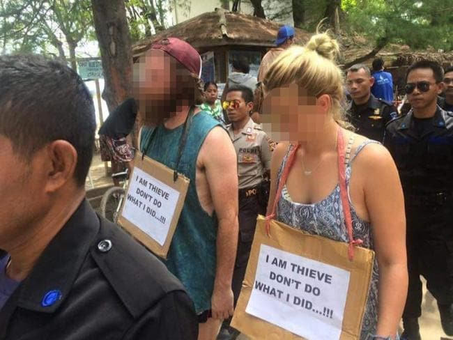 The tourists were made to wear signs that read: 'I am thieve (sic) don't do what I did...!!!'. Picture: Facebook/Gili Trawangan, Meno, Air