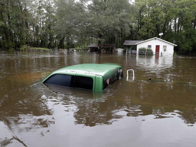 A vehicle and a home are swamped with floodwater from nearby Black Creek in Florence, South Carolina. Picture: AP Photo/Gerry Broome