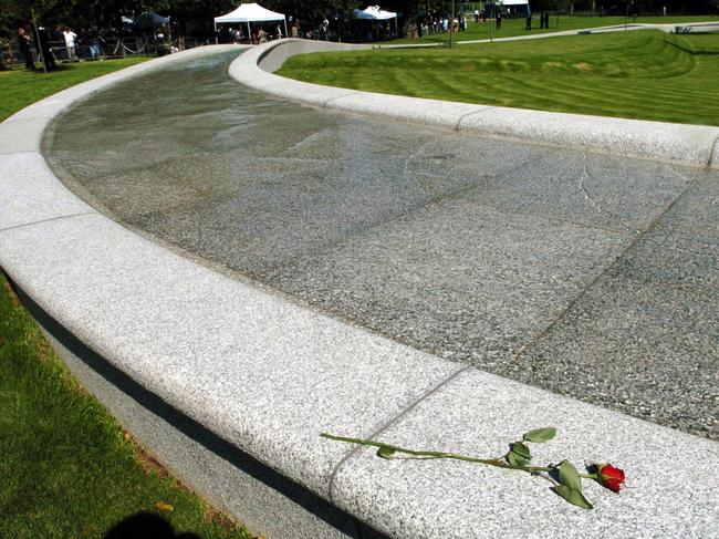 A single rose is left at the memorial after the unveiling ceremony for the memorial fountain.