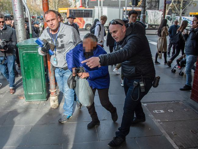 A woman breaks down while being escorted by police. Picture: Jason Edwards