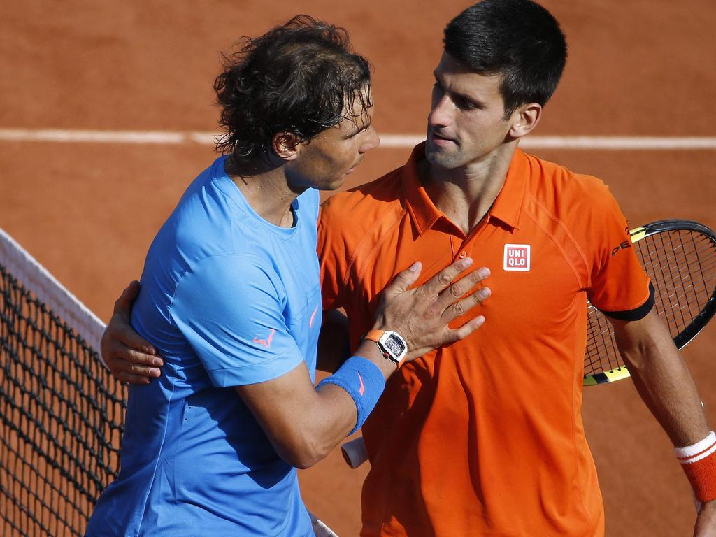 (FILES) In this file photo taken on June 03, 2015 Spain's Rafael Nadal (L) shakes hands with Serbia's Novak Djokovic at the end of their men's quarter final match of the Roland Garros 2015 French Tennis Open in Paris. - Spain's Rafael Nadal and Serbia's Novak Djokovic will play against each other on June 11, 2021 in the men's singles semi-final tennis match of The Roland Garros 2021 French Open tennis tournament in Paris. (Photo by Kenzo TRIBOUILLARD / AFP)