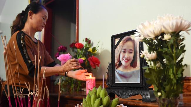 A relative lights an incense stick in front of a portrait of Bui Thi Nhung, who is thought to be among the dead. Picture: NHAC NGUYEN / AFP.