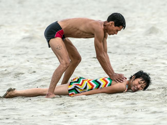 A man gives his wife a massage on the beach on August 22, 2018 in Wonsan, North Korea. Picture: Carl Court/Getty Images