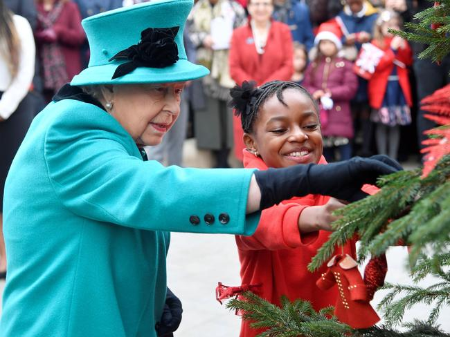 Queen Elizabeth II helped Shylah Gordon attach a bauble to a Christmas tree at children's charity, Coram.