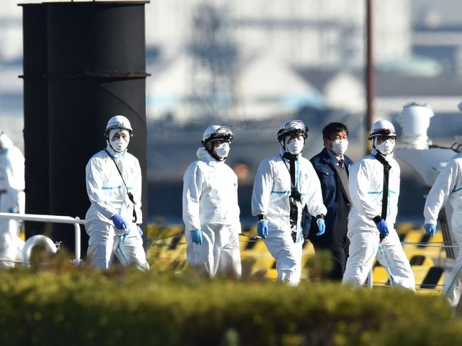 Personnel clad in protective gear, tasked to provide care for suspected patients on board the Diamond Princess cruise ship, are seen at the Japan Coast Guard base in Yokohama. Picture: Kazuhiro Nogi/AFP.