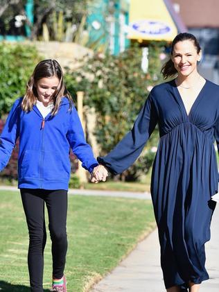 Garner holds hands with her middle child, Seraphina. Picture: Boaz/Backgrid