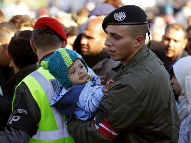 Dangerous journey ... A member of the Austrian army holds a baby as migrants wait for transport at the Austrian border with Slovenia in Spielfeld, Austria. Picture: REUTERS/Leonhard Foeger