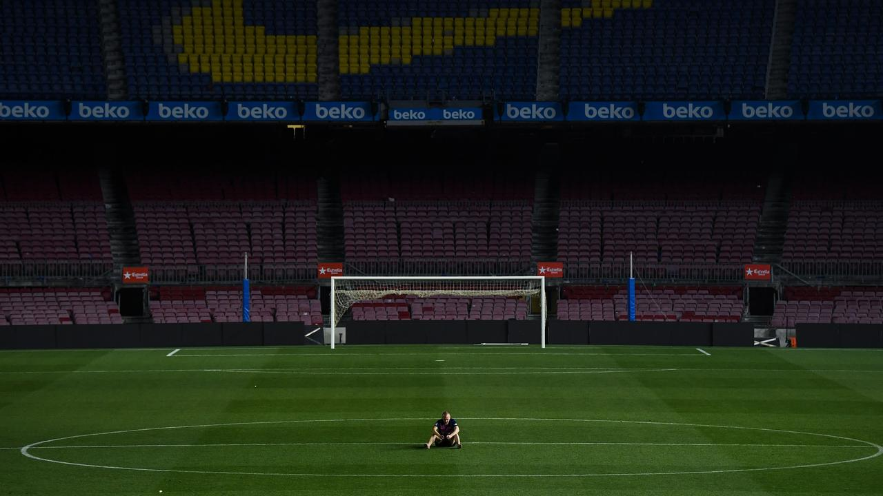 Andres Iniesta sits on the pitch at the Camp Nou after his last game for Barcelona.