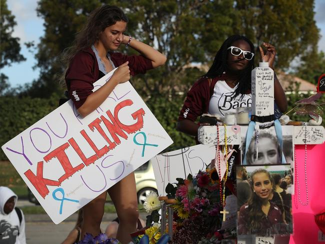Haleigh Grose, a 9th grader at Marjory Stoneman Douglas High School, holds a sign that reads, 'You are Killing Us,' as she visits the memorial set up in front of the school where 17 people that were killed. Picture: Getty