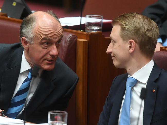 Senator Eric Abetz (left) speaks to Senator James Paterson during Senate Question Time in the Senate chamber at Parliament House. Picture: AAP
