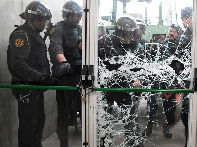 Spanish Civil Guard officers break through a door at a polling station for the banned independence referendum. Picture: AFP/Lluis Gene