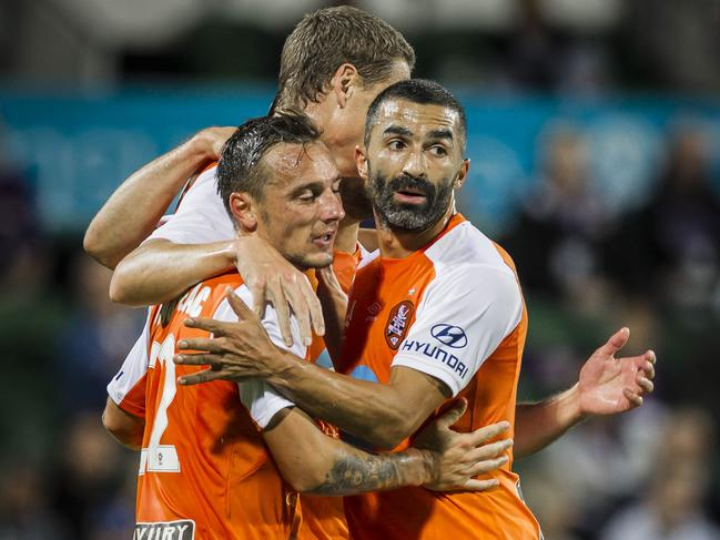 Brisbane Roar players Eric Bautheac (left), Fahid Ben Khalfallah (right) and Thomas Thomas Kristensen celebrate a Roar goal.
