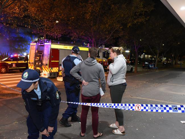 Worried residents evacuated from the complex in Sydney's inner south speak to police outside the building. Picture: Flavio Brancaleone