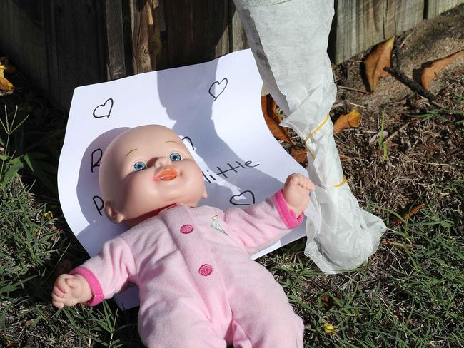 Flowers, doll and a note left at the house of the victims of a fatal car fire. Picture: Liam Kidston