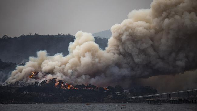 Fires burning at Eden on Monday morning as the HMAS Adelaide arrived with supplies for communities on the far south coast. Picture: Gary Ramage