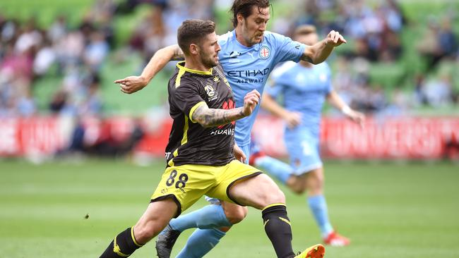 Gary Hooper of Wellington Phoenix and City's Joshua Brillante compete for the ball.