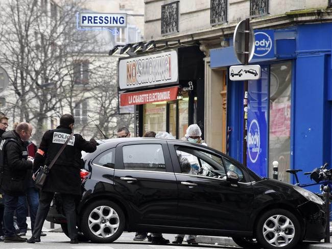Investigation ... French police and forensic experts examine the car used by armed gunmen who stormed the Paris offices of Charlie Hebdo. Picture: AFP/Getty Images