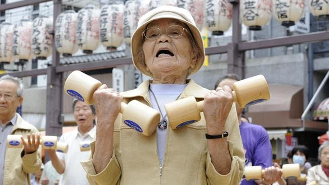 Elderly people work out with wooden dumbbells in the grounds of a temple in Tokyo on September 21, 2009 to celebrate Japan's Respect-for-the-Aged-Day. Picture: AFP / Yoshikazu Tsuno.