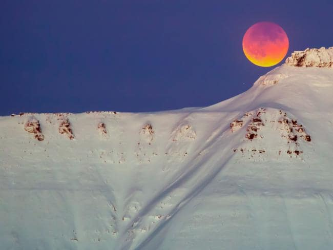 A super blue blood moon rises from behind a mountain near Longyearbyen, Svalbard, Norway. Picture: AFP