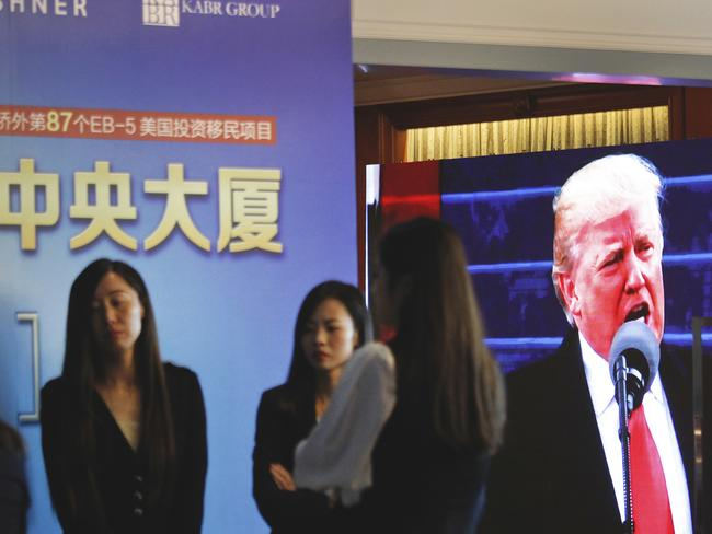 A projector screen shows a footage of US President Donald Trump as workers wait for investors at a reception desk during an event promoting EB-5 investment in a Kushner Companies development at a hotel in Shanghai, China. Picture: AP Photo