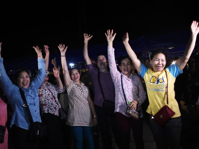 Volunteers at the site celebrate after the last of the boys and their coach were freed. Picture: AFP