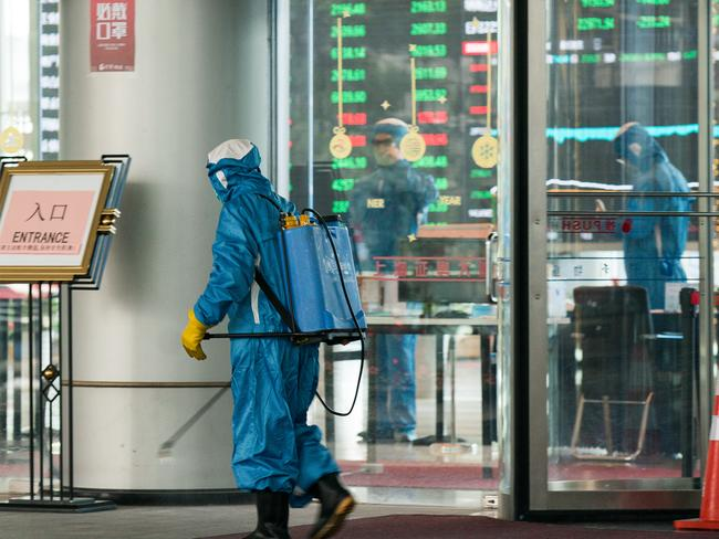 A medical worker sprays antiseptic outside of the front gate of Shanghai Stock Exchange Building. Picture: Yifan Ding/Getty Images.